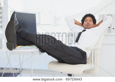 Businessman relaxing in his swivel chair with feet up in his office