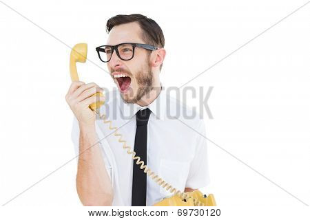 Geeky businessman shouting at telephone on white background