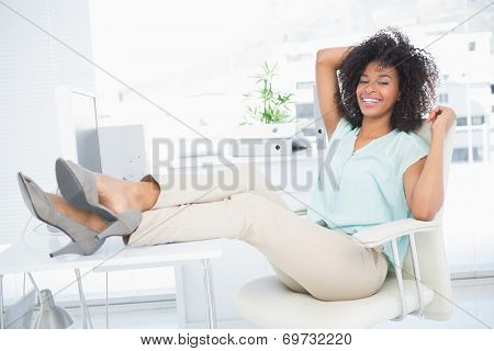Happy businesswoman sitting with her feet up in her office