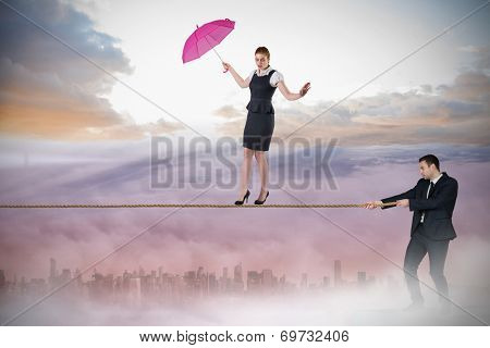 Young businessman pulling a tightrope for businesswoman against cityscape in the clouds