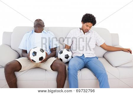 Distraught football fans sitting on the couch with balls on white background