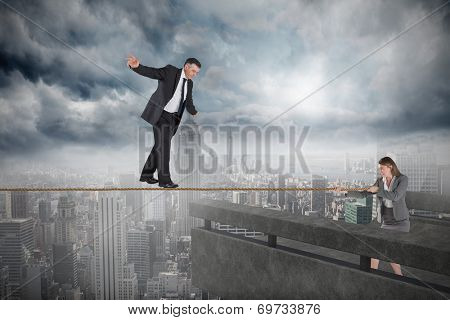 Young businesswoman pulling a tightrope for businessman against balcony overlooking city