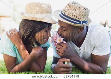 Happy couple lying in garden together smelling flowers on a sunny day