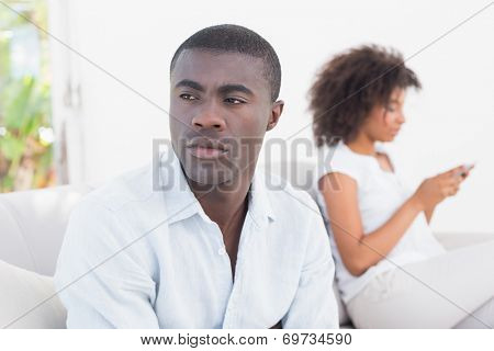 Attractive couple having an argument on couch at home in the living room