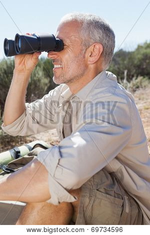 Hiker taking a break on country trail looking through binoculars on a sunny day