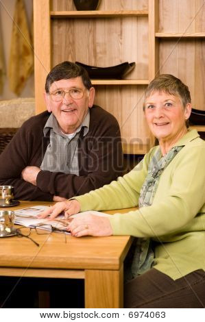 Senior Couple Sitting In Dining Room