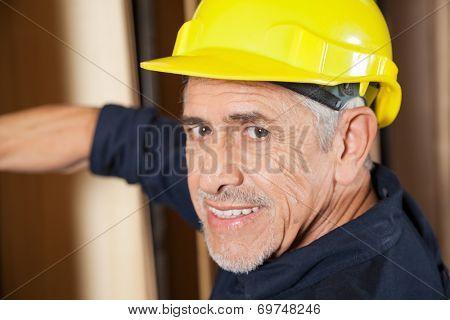 Closeup portrait of senior carpenter smiling in workshop