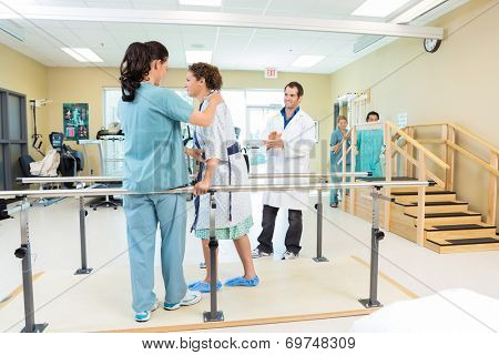 Mid adult female patient being assisted by physical therapist while doctor applauding