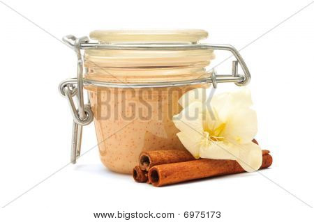 Closed Jar With Some Creamy Substance, White Flower And Cinnamon On A White Background