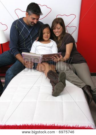 Family Reclining In Bed Reading