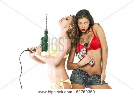 Portrait of Two sexy girls holding a power drill