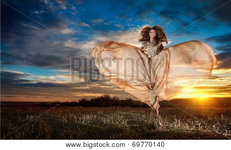 Fashionable beautiful young woman in nude colored long dress spinning around looking as a butterfly