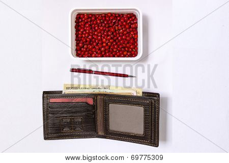 Background of purse/wallet, a red colour pen and red seeds