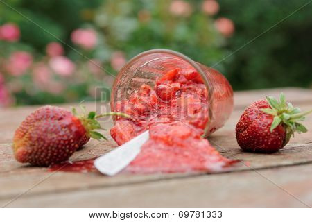 Strawberry smoothie spilled from glass on wooden table
