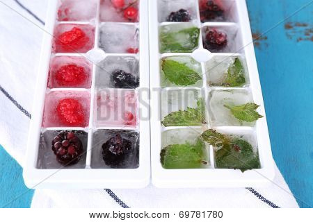 Ice cubes with forest berries, mint leaves in ice cube tray, on color wooden background