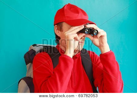 A Trekker During An Excursion Looking Through His Binoculars