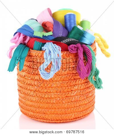 Round orange box full of multicoloured threads and everything necessary for sewing on white background isolated