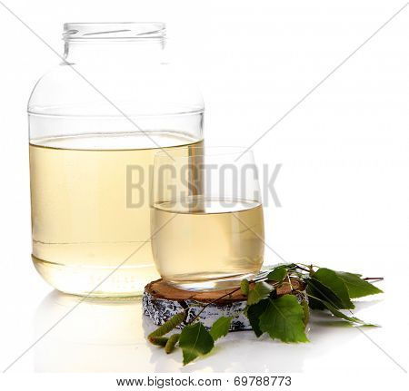 Glass and large flagon of fresh birch sap isolated on white