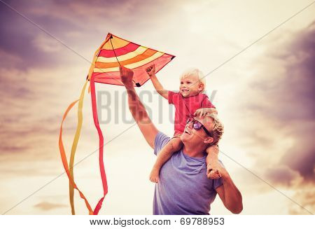 Son on Father's Shoulder at Sunset Flying a Kite Together