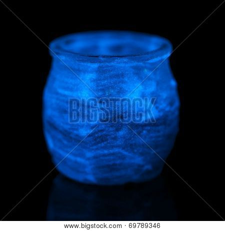 Candlestick painted fluorescent paint isolated on black
