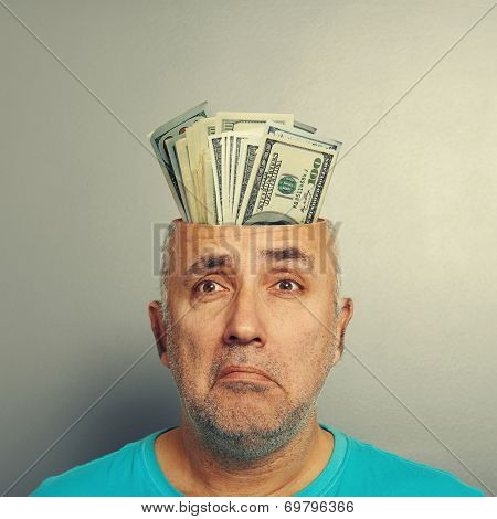 depressed senior man having open head with money over grey background