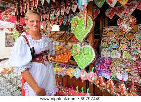 DOMAZLICE CZECH REPUBLIC - AUGUST 9, 2014: Unidentified woman buying sweet gingerbread on The Chodske slavnosti medieval market. Traditional homemade product from Czech countryside.