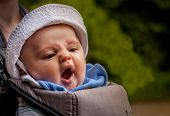stock photo of boredom  - Baby boy yawning while being carried by his mother in a sling