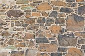 foto of stonewalled  - Antique natural stonewall old stones in different sizes - JPG
