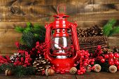 stock photo of kerosene lamp  - Red kerosene lamp on wooden table on wooden background - JPG