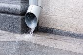 foto of rain  - Rain water flowing from a metal downspout during a heavy rain - JPG