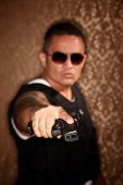 stock photo of gangster necklace  - Hispanic Cop Pointing Gun at Camera Gangster Style - JPG