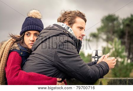 Young couple embracing and having hot beverage outdoors