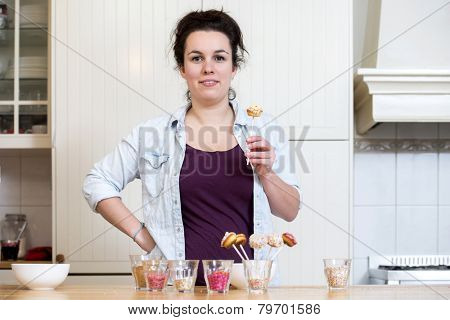 Portrait of woman holding cupcake pop at kitchen counter