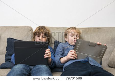 Boys playing online games on digital tablets while relaxing on sofa at home