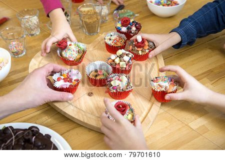 Kids picking their favourite decorated cupcake from a heart shaped cutting board at a birthday party