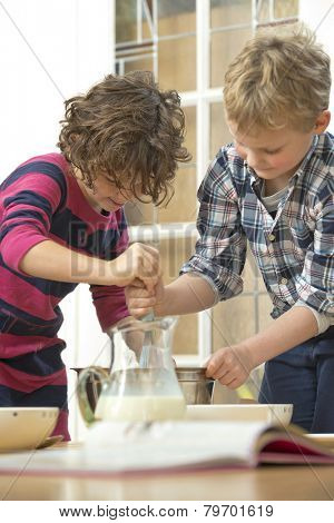 Two kids whisking batter in a bowl during a baking workshop at home at a birthday party.