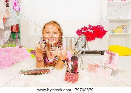 Beautiful girl on carpet and applying lip gloss