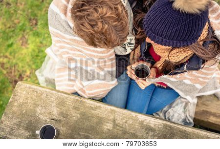 Young couple under blanket having hot drink in a cold day