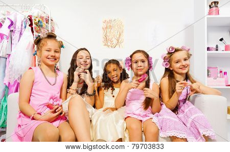Charming girls with hair-curlers sitting on sofa