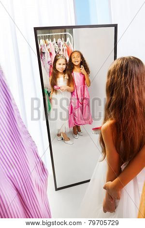 Two little girls with dresses in the mirror