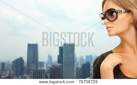 people, fashion, eyewear and style concept - beautiful woman in shades over city background