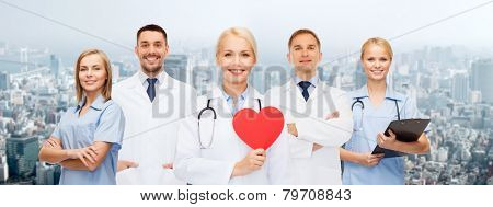 medicine, profession, teamwork and healthcare concept - group of smiling medics or doctors holding red paper heart shape, clipboard and stethoscopes over city background
