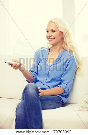 television, relax, home and happiness concept - smiling young girl sitting on couch with tv remote control at home