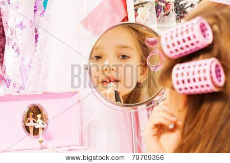 Cute girl making up her face looking in mirror
