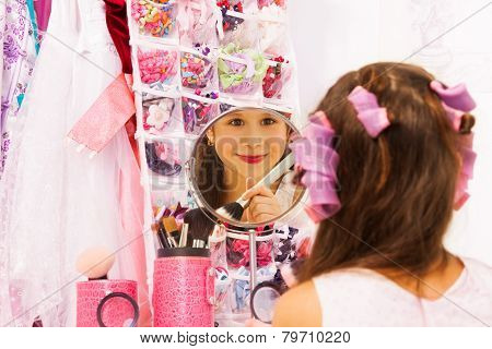 Smiling attractive girl making up face in mirror