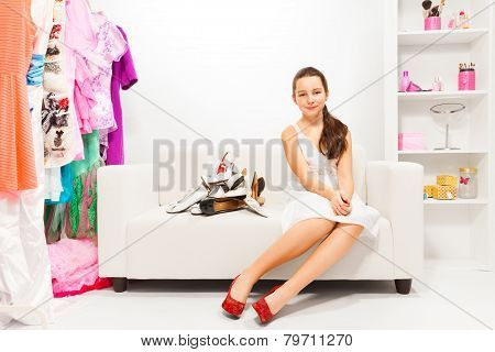 Girl trying to choose shoes in the pile of them