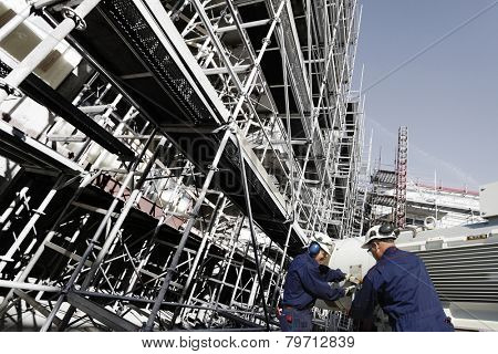 building workers with machinery inside large scaffolded site