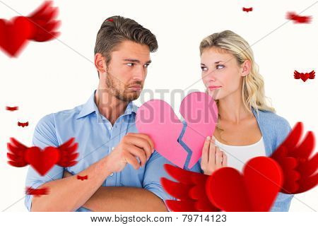 Couple holding two halves of broken heart against hearts