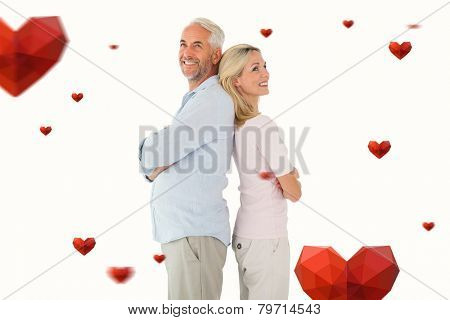 Smiling couple standing leaning backs together against hearts