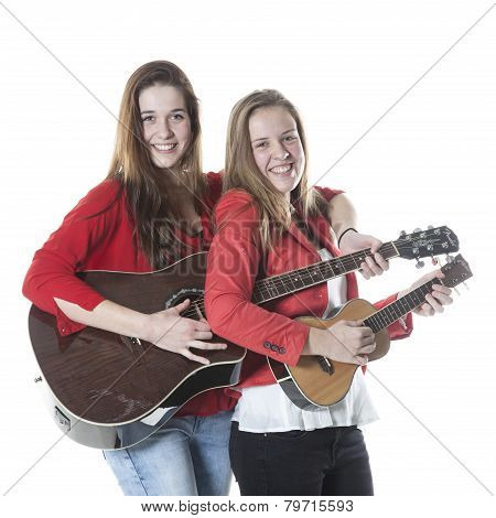 Two Teenage Sisters Play Ukelele And Guitar In Studio
